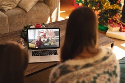 Rear view of woman and son having a videocall with man and son in santa hats waving on laptop at hom
