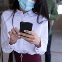 Businesswoman wearing face mask using smartphone