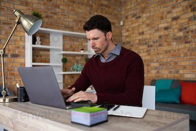 Man using laptop while sitting on his desk