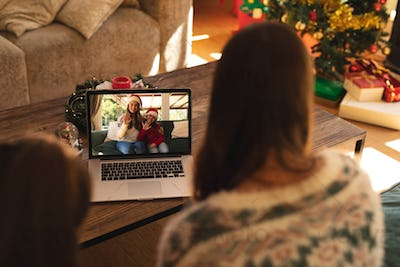 Rear view of woman and son having a videocall with woman and daughter in santa hats waving on laptop