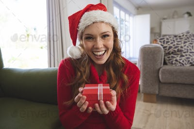 Portrait of woman wearing Santa hat holding a gift box at home