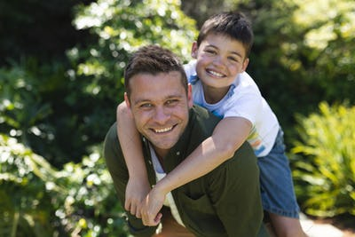 Portrait of caucasian man and his son spending time in their garden together