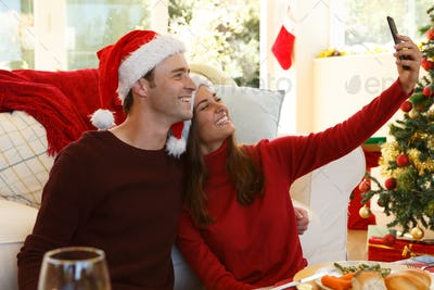 Couple wearing santa hat talking a selfie from smartphone while sitting in the living room at home