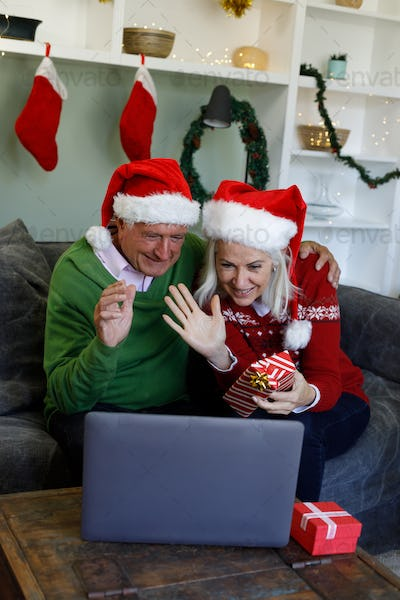 Senior couple in santa hat sitting on couch holding gift box waving while having a video call on lap