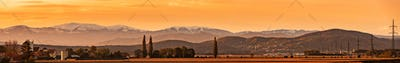 Styrian Lavanttaler Alps covered with snow in orange light of sunset. Panorama Background