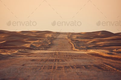 Empty desert road in the middle sand dunes