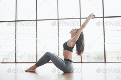 A sports girl who cuts the torso and makes a stretch. A woman tries to be in good shape