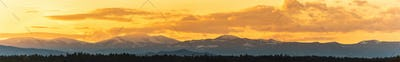 Styrian Lavanttaler Alps covered with snow in orange light of sunset. Background or banner