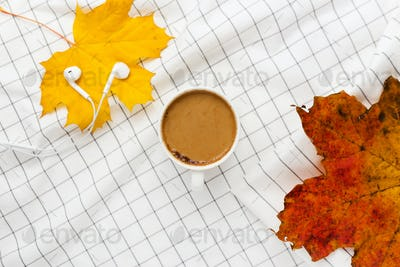 Autumn composition. Cup of coffeecup, autumn leaves and earphones on white checkered cloth