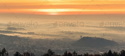 Panorama of Graz city covered if fog on autumn morning during sunraise