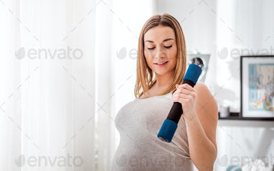 Pregnant woman doing exersice at home using dumbells