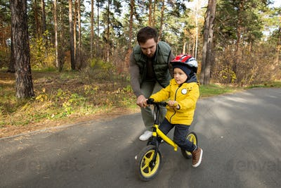 Young father slightly bending while helping his little son to ride balance bike