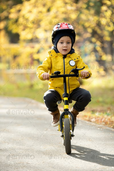 Adorable little boy in casualwear and protective helmet sitting on balance bike