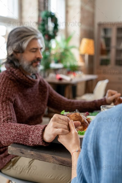 Hands of young woman and mature bearded man praying before Christmas dinner