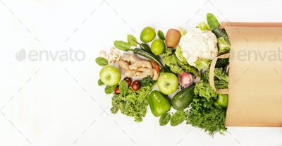 Green vegan food in full paper shopping bag, vegetables and fruits on white background