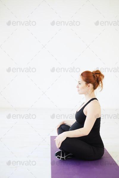 Pregnant woman sitting in lotus pose relaxing