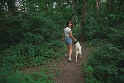 Young modern woman hiking with a dog in the summer landscape. Friendship, people, animals
