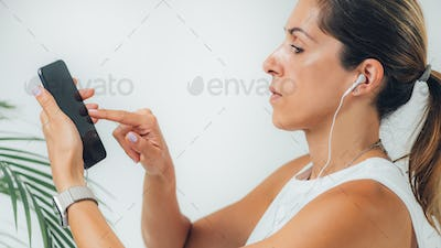 Woman Doing Audiogram Hearing Test at Home, using Smart Phone and App.