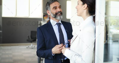 Happy business colleagues in modern office smiling and talking