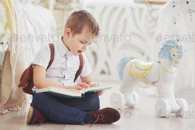 Cute little boy is going to school for the first time. Child with bag and book. Kid makes a