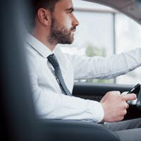 Satisfied young business man looking at mobile phone while driving a car