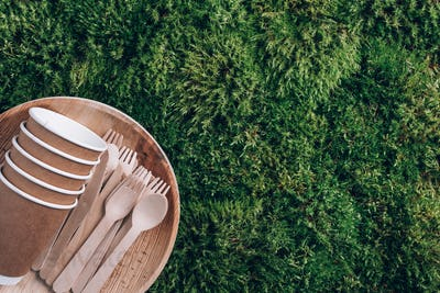 Disposable tableware from natural materials. Bamboo plates, wooden spoon, fork, knife, paper cups on
