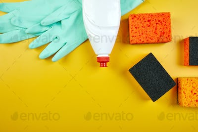 Flat lay of  cleaning set for dish washing yellow background with copy space