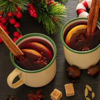 Mulled wine, Christmas hot drink in mugs on black stone, closeup view