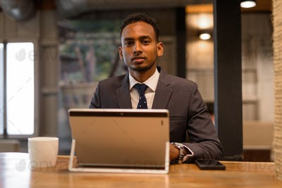 Young African businessman using laptop computer at coffee shop