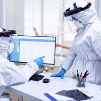 Dentist assistant in ppe suit pointing at patient waiting list