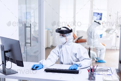 Nurse using computer during covid 19 wearing ppe suit