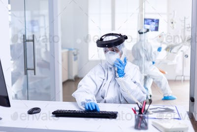 Dentist nurse in ppe suit discussing with patient on the phone