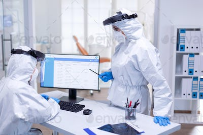 Dentist doctor wearing ppe suit talking with nurse at reception