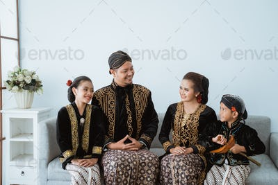 Portrait of a happy family wearing traditional Javanese clothes