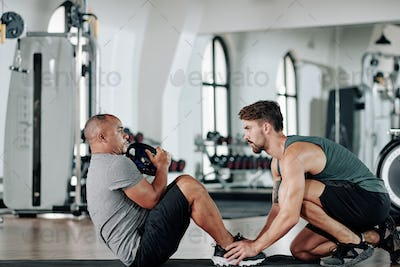 Fitness trainer helping mature client
