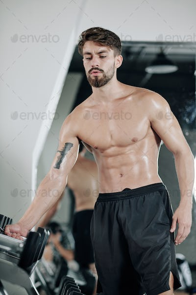 Man taking dumbbell from stand