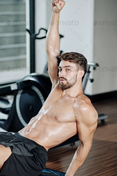 Fit man sitting on bench in gym