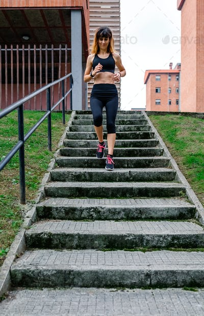 Female athlete going down stairs outdoors