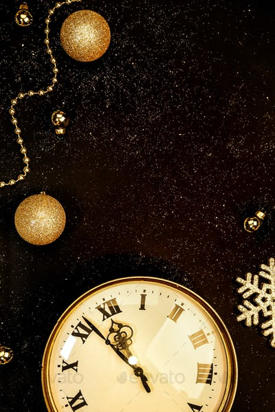 Gold vintage clock decorated with christmas balls on a black background in sparkles, new year's eve