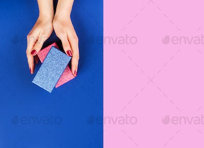 Hands with gift box on pink and classic blue