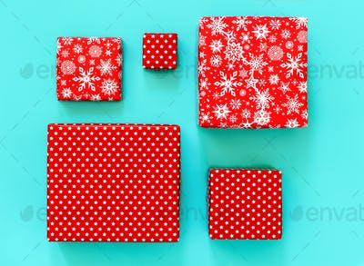 Gift boxes wrapped in red paper on light green background