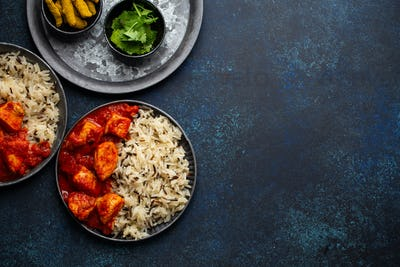 Chicken tikka masala dish with rice, flat Indian bread and spices