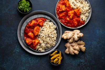 Chicken tikka masala dish with rice, flat Indian bread and spices in rustic metal plates
