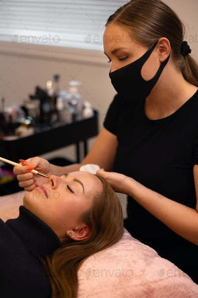 Eyelash extension procedure with master and a client in a beauty salon