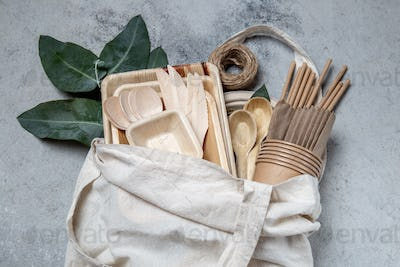 Eco craft paper and wooden tableware. Paper cups, dishes, bag, plates and wooden cutlery in linen