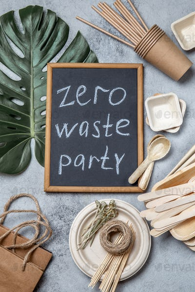 Zero waste party concept. Eco ffriendly tableware, craft bags and monstera leaves on gray background
