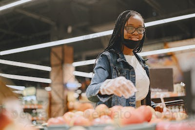 Black girl in a mask buy a food