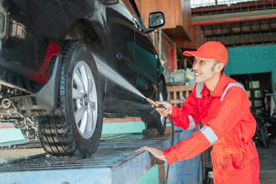 Smiling Asian male car cleaner wearing red uniform and hat is spraying water on a car