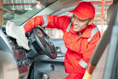 Male car cleaner wearing red uniform is wiping car interior dashboard