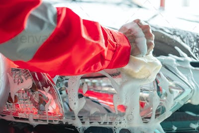 close up of car cleaner hands in red uniforms cleaning car windows with a foamy sponge